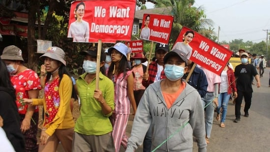 Protesters marching ahead holding signs with portraits of detained Myanmar civilian leader Aung San Suu Kyi during a demonstration against the military coup in Launglon township in Dawei.(AFP Photo)