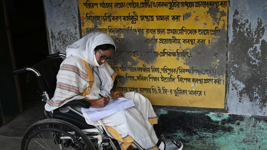 West Bengal's Chief Minister Mamata Banerjee takes notes while sitting in a wheelchair at a polling station during Phase 2 of West Bengal's legislative election in Nandigram on April 1, 2021. (AFP Photo )