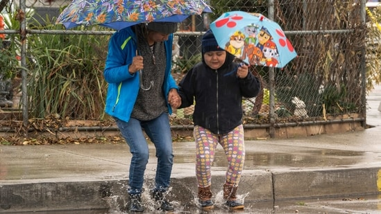 Mariella Velazquez plays with her daughter Elisa Medina, 11, who has autism, jump under the rain in El Monte, California. (AP)
