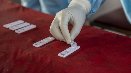 A health worker tests a swab sample for Covid-19 infection, in Srinagar, on March 30. The number of active cases in India went up by 11,846, and currently stand at 5,52,566, health ministry's data showed.(Dar Yasin / AP)