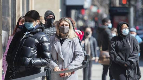 People wear face masks as they wait to enter a store in Montreal, on Friday. (AP)