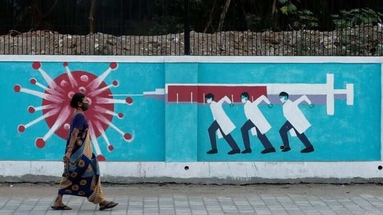 A woman wearing a protective face mask walks past a graffiti, amidst the spread of the coronavirus disease (COVID-19), on a street in Mumbai, India, March 30, 2021. REUTERS/Francis Mascarenhas/Files(REUTERS)