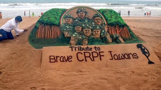 Sand artist Sudarsan Pattnaik creates a sand sculpture as tribute to CRPF jawans killed in Chhattisgarh Maoist attack, at Puri beach of Odisha on Sunday.(PTI Photo)
