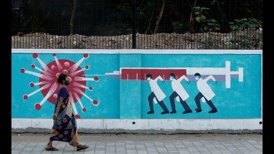 A woman wearing a protective face mask walks past a graffiti, amid the spread of the coronavirus disease, Mumbai, March 30, 2021. (REUTERS)
