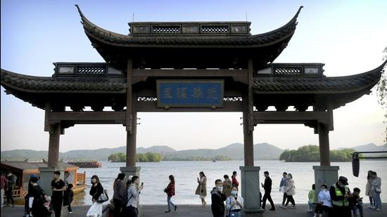 Visitors wearing masks walk near a gate at the West Lake in Hangzhou in eastern China's Zhejiang Province, on Sunday. (AP)