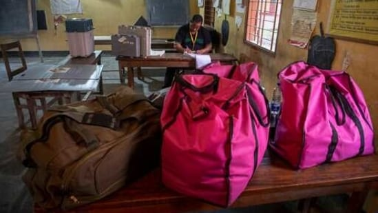 Polling officials make preparations at a polling station on the eve of third phase of assembly election, in Assam's Guwahati on Monday.(AP Photo)