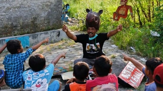 Samsudin, 50, wearing a rhino-hat holds cupboard puppets depicting Indonesia's endemic primates orangutan and long tail monkey, while performing fairy tales for the local children in Indramayu regency, West Java province, Indonesia.(REUTERS)