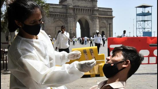 A healthcare worker collects a nasal sample from a man to test for Covid-19 . (ANI)