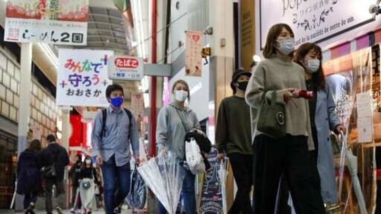 People wearing face masks to help curb the spread of the coronavirus walk at Umeda's downtown area in Osaka, western Japan, Sunday, April 4, 2021. (AP)
