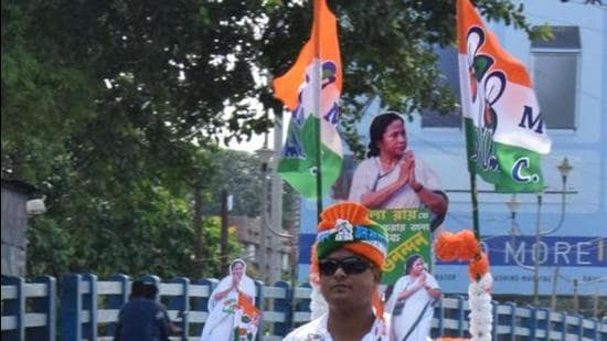 A TMC supporter rides a scooty with a cut-out of West Bengal chief minister Mamata Banerjee and party flags in Kolkata. (ANI)