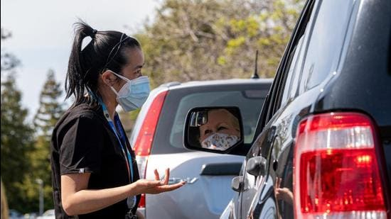 A health care worker speaks with a person in the observation area of a mobile drive-thru Covid-19 vaccination site in Novato, California. (Bloomberg)