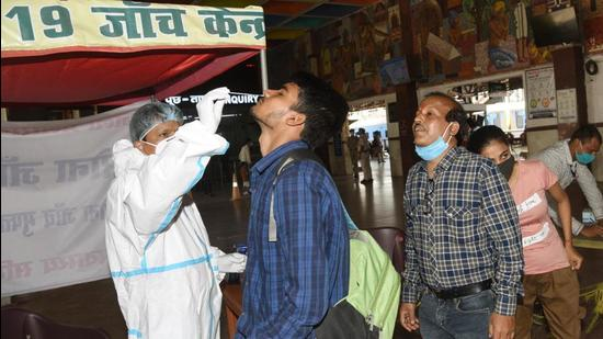 A medic collect swab samples of passengers for Covid-19 testing at Patna Junction on April 4. (Santosh Kumar /Hindustan Times)