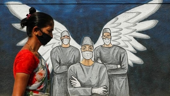 A woman wearing a face mask walks past a Covid-19 graffiti in Navi Mumbai.( REUTERS)
