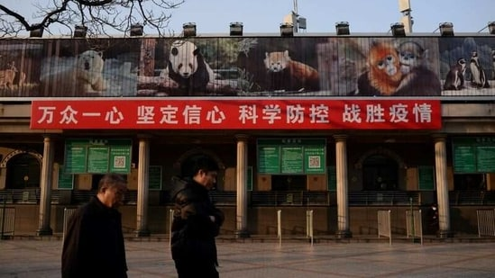 Men walk past a banner hung on the ticket office of the Beijing Zoo that is closed following an outbreak of the novel coronavirus in the country, in Beijing, China.(Reuters)