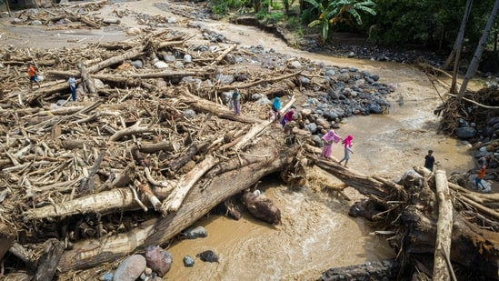 An aerial picture shows people walking through a pile of tree trunks after flash floods triggered by tropical cyclone Seroja in East Flores, East Nusa Tenggara province, Indonesia April 7, 2021, in this photo taken by Antara Foto/Aditya Pradana Putra via REUTERS ATTENTION EDITORS - THIS IMAGE WAS PROVIDED BY THIRD PARTY. MANDATORY CREDIT. INDONESIA OUT.(Via REUTERS)