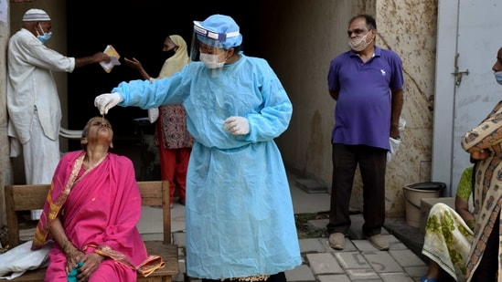 Mumbai, India - April 7, 2021: A BMC health care worker taking a swab smaple from a hawker to test for Covid-19 at Govandi in Mumbai, India, on Wednesday, April 7, 2021. (Photo by Satish Bate/Hindustan Times)(Satish Bate/HT Photo)
