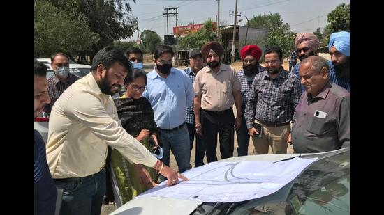 Councillor Mamta Ashu and GLADA officials examining the blueprint of the project to widen the bridge over Sidhwan Canal, near Jhammat village in Ludhiana. (HT Photo)