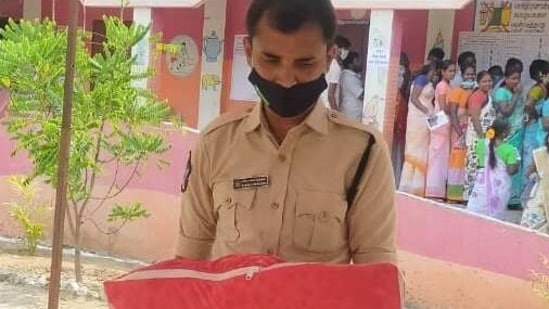 The image shows the Anantapur constable holding the baby outside a polling booth during Tamil Nadu Assembly elections 2021(Twitter/@APPOLICE100)