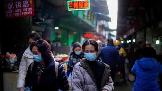 Covid-19 in China: People wearing face masks walk on a street market in Wuhan, Hubei province. (File Photo: Reuters)