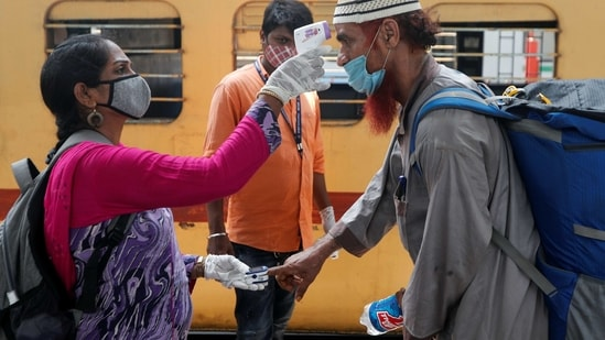 A health worker checks a passenger's temperature and pulse at a railway station in Mumbai.(Reuters)