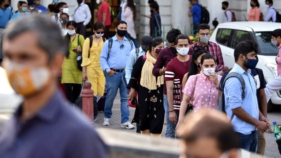 Commuters stand in a long queue outside a metro station at Connaught Place while entering in small groups as a preventive measure against the Covid-19, in New Delhi on Thursday. (ANI Photo)