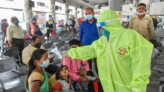 Lucknow: A health worker checks temperature of passengers as part of precautions against Covid-19, at bus station.(PTI file photo)