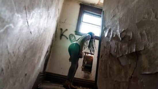 Larrecsa Cox peers around a stairwell while walking through an abandoned home frequented by people struggling with addiction.(AP)