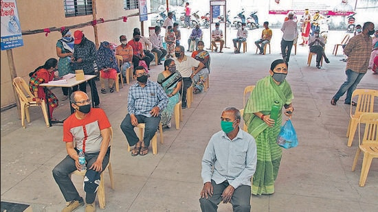 People wait outside a Covid vaccination centre in Pune , on Friday. (RAVINDRA JOSHI/HT)