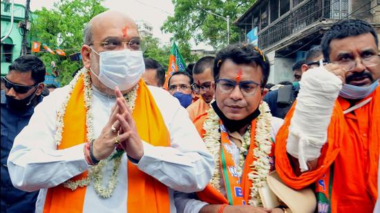 Union Home Minister and BJP leader Amit Shah during his door-to-door election campaign in favour of party candidate from Bhawanipore assembly constituency Rudranil Ghosh, in Kolkata on Friday. (PTI PHOTO.)