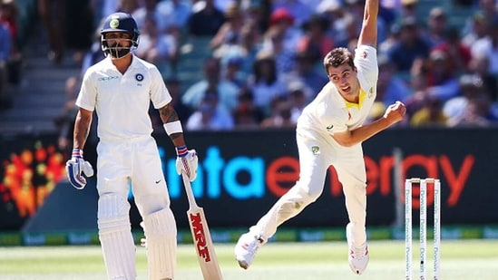 Pat Cummins bowls as Virat Kohli looks on at the non-striker's end. (Getty Images)