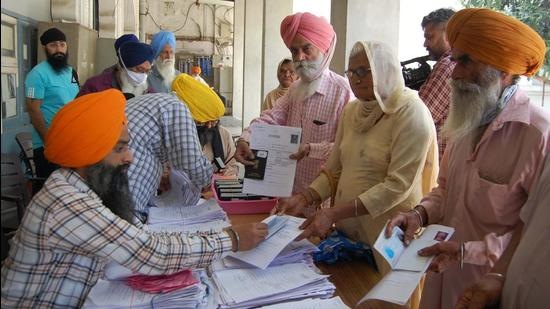 Sikh pilgrims collect their passports from Shiromani Gurdwara Parbandhak Committee (SGPC) officials at the Golden Temple complex in Amritsar on Sunday. (Sameer Sehgal/HT)
