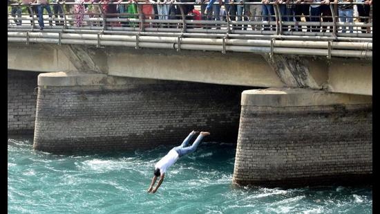 A protester jumps into the Bhakra canal during a demonstration by unemployed TET-pass BEd teachers against the Punjab government, in Patiala on Sunday. (PTI)