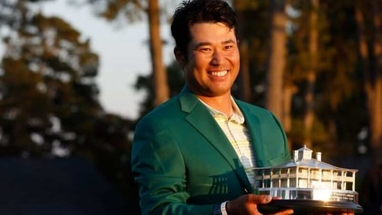 Japan's Hideki Matsuyama celebrates with the green jacket and the trophy after winning The Masters.(REUTERS)