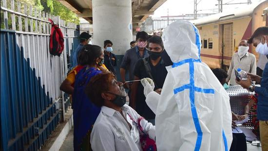 A health worker wearing protective gear conducts Rapid Antigen test for Covid-19 of passengers. (Bhushan Koyande/ HT Photo)