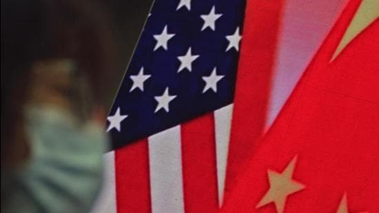 A file photo of a woman in a face mask near a screen showing China and US flags in Beijing. (AP)