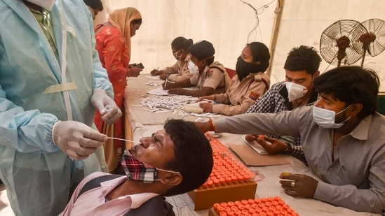 A health worker conducts COVID-19 testing of a passenger, as coronavirus cases surge across the national capital, at Anand Vihar Bus Terminal in New Delhi. (PTI Photo)