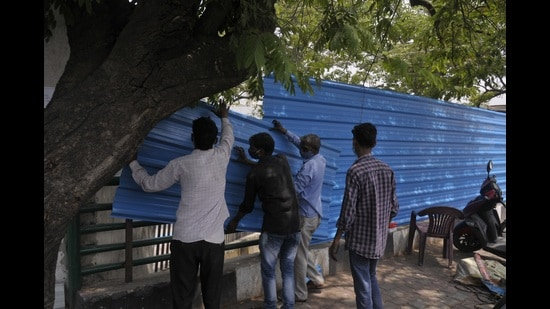 Tin sheets being installed to block the view of Bhainsakund cremation site in Lucknow. (Deepak Gupta/HT Photo)