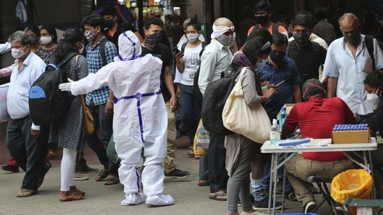 So far, 23,170,964 samples have been tested for the coronavirus disease in Karnataka. In picture - Health worker directs arriving passengers towards Covid-19 testing counter outside a train station in Bengaluru. (AP)