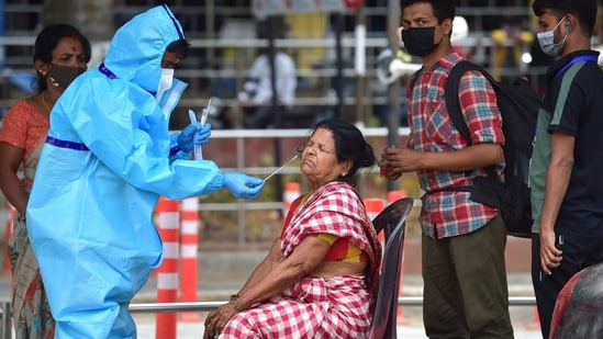 A medic collects samples for COVID-19 tests at Bengaluru City Railway Station, amid surge in coronavirus cases in Bengaluru on Wednesday.(PTI)