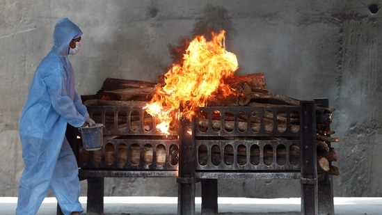A frontline worker in personal protective equipment (PPE) sprays a flammable liquid on a burning funeral pyre of a man who died from the coronavirus disease (COVID-19), at a crematorium.(REUTERS)