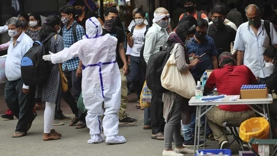 So far, 23,170,964 samples have been tested for the coronavirus disease in Karnataka. In picture - Health worker directs arriving passengers towards Covid-19 testing counter outside a train station in Bengaluru.