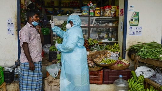 A health worker taking a swab sample from a shopkeeper for a RT-PCR Covid-19 coronavirus test in Chenna.(AFP)