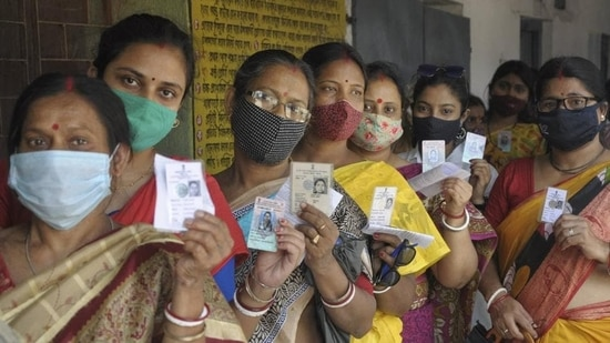 Women show their voter ID cards as they stand in a queue to cast their vote at a polling station during the 5th phase of West Bengal assembly polls.