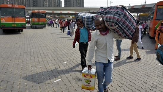 Migrant workers and other travellers leaving the city as Covid-19 cases in the NCR region rise, at Kaushambi Bus Terminal in Ghaziabad.(Sakib Ali / HT Photo)