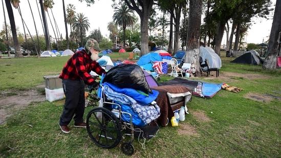 A homeless man pushes his belongings at a homeless encampment at Echo Park Lake in Los Angeles, California. (AFP)