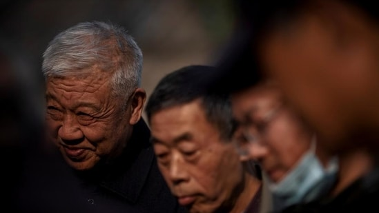 Elderly people watch a game of mahjong in Beijing, China (Reuters)