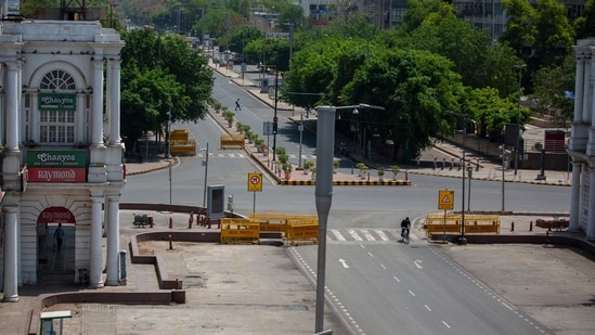 A cyclist pedals past a deserted street during a weekend lockdown in New Delhi, India, Saturday, April 17, 2021. (AP)