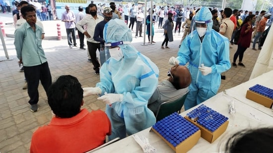 Health workers take swab samples of people for Covid-19 test amid the surge in coronavirus cases, at Anand Vihar Terminal in New Delhi.