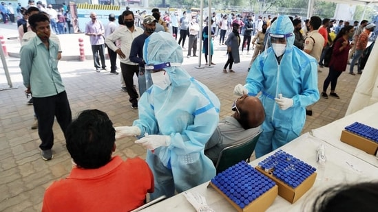 Health workers take swab samples of people for Covid-19 test amid the surge in coronavirus cases, at Anand Vihar Terminal in New Delhi.(ANI)