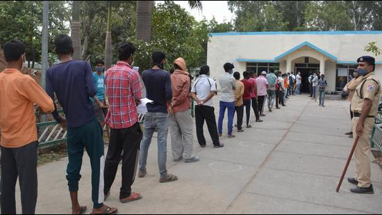 Amid lockdown announcement and fear of more curbs, migrant workers lined up outside the reservation counter to book tickets for travelling back home at the railway station in Chandigarh on Tuesday. (Sant Arora/HT)